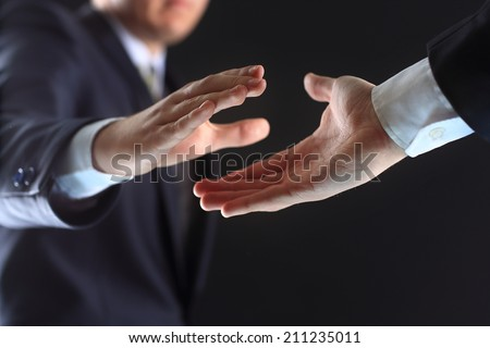 Photo of hands of business partners before handshake in black background - stock photo