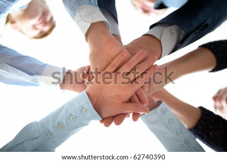 Photo of hands on top of each other above camera - stock photo