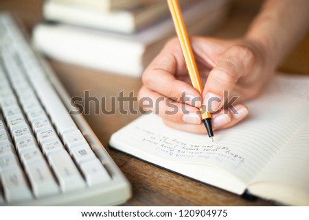 Photo of hands writes a pen in a notebook, computer keyboard and a stack of books in background - stock photo