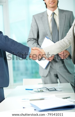 Photo of handshake of business partners after striking deal on background of elegant man - stock photo