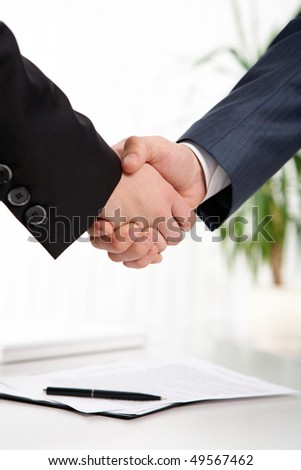 Photo of handshake of business partners after striking deal on background of signed documents - stock photo