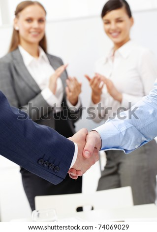 Photo of handshake of business partners after striking deal on background of two women applauding - stock photo