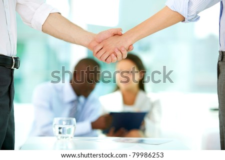 Photo of handshake of business partners after striking deal on background of working people - stock photo