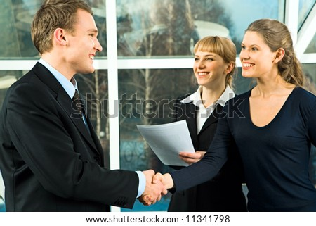 Photo of handshake of businesspeople with their smiling in the office