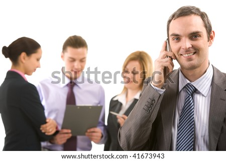 Photo of handsome employer calling his partner with working employees behind - stock photo
