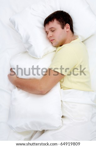 Photo of handsome man sleeping and holding soft white pillow - stock photo