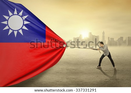 Photo of handsome man with casual clothes, pulling Taiwan national flag - stock photo