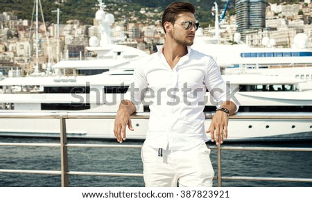 Photo of handsome man with luxury yacht in port - stock photo