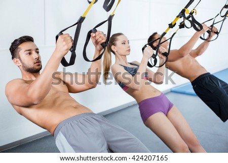Photo of handsome men and beautiful woman. Sporty people training with TRX Suspension at fitness club - stock photo