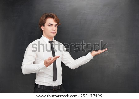 Photo of handsome young man on blank chalkboard background. Man looking at camera and pointing at chalkboard with two hands - stock photo