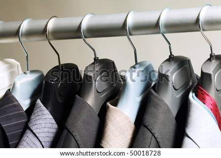Photo of hangers with jackets on them in boutique - stock photo