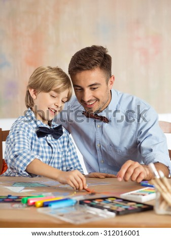 Photo of happy artistic siblings in bow ties drawing together - stock photo