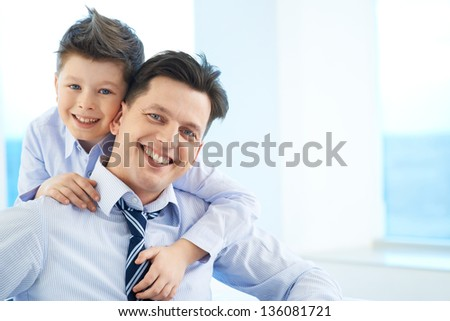 Photo of happy boy embracing his dad and both looking at camera