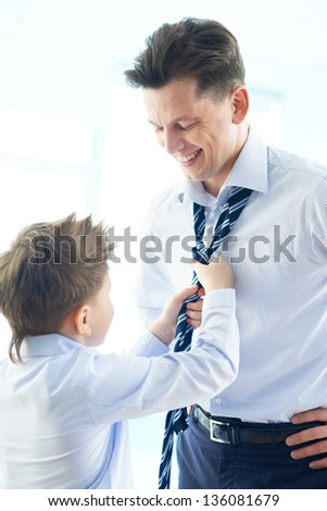 Photo of happy boy helping his father tie necktie - stock photo
