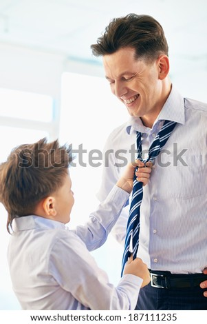Photo of happy boy helping his father tie necktie - stock photo