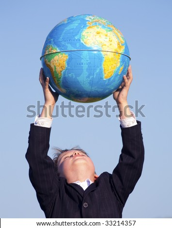 Photo of happy boy raising globe in hands while standing under blue sky