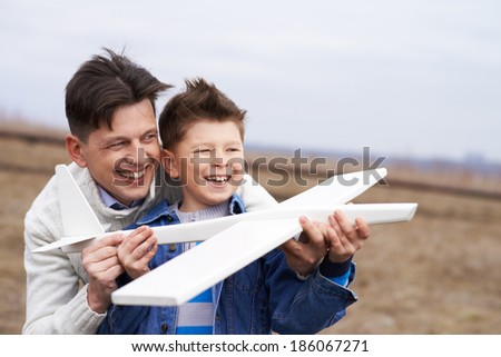 Photo of happy boy with toy airplane and his father playing together - stock photo