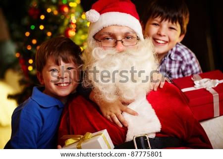 Photo of happy boys and Santa Claus looking at camera - stock photo
