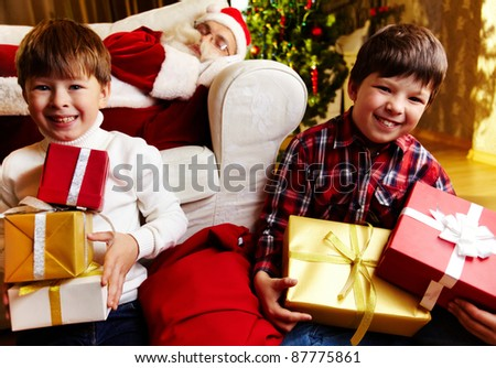 Photo of happy boys holding gifts with Santa Claus sleeping on sofa on background - stock photo