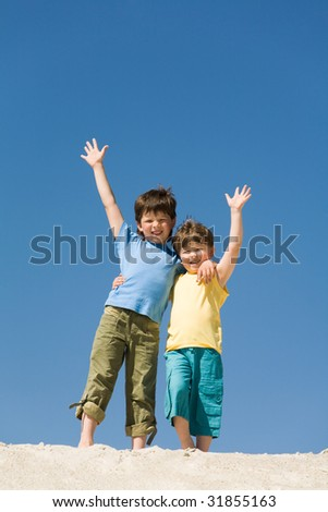 Photo of happy boys waving on sandy beach and looking at camera - stock photo