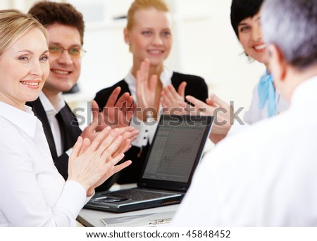 Photo of happy business partners applauding to their senior leader after making report - stock photo