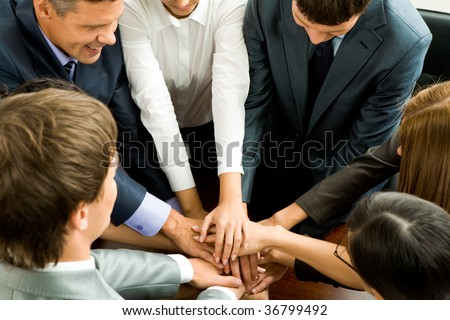 Photo of happy business partners making pile of hands on workplace - stock photo