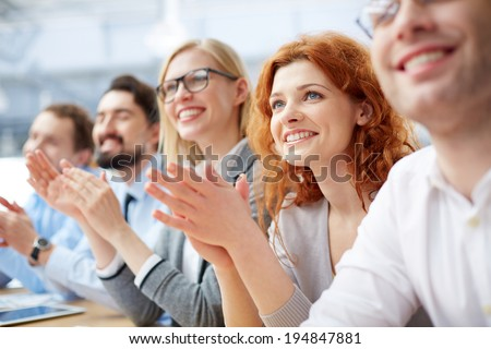 Photo of happy business people applauding at conference, focus on smiling girl - stock photo