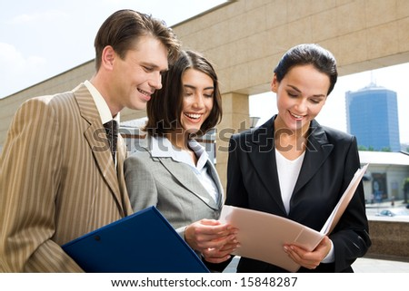 Photo of happy businesspeople communicating with each other while looking through documents