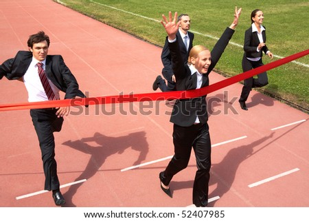 Photo of happy businesswoman crossing finish line during race - stock photo