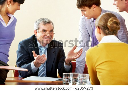 Photo of happy chief explaining work to subordinate persons - stock photo