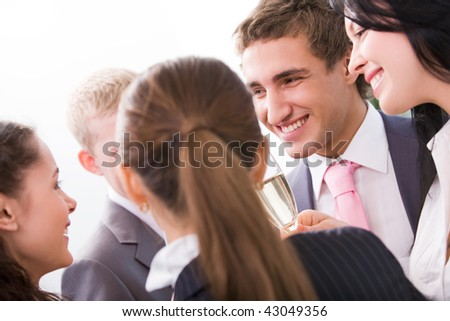 Photo of happy colleagues holding flutes with champagne and smiling while toasting at party - stock photo
