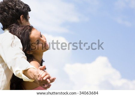Photo of happy couple holding each other by hands over blue sky - stock photo
