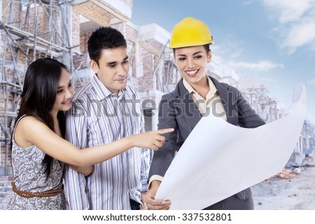 Photo of happy couple looking at blueprint of new house with their architect - stock photo