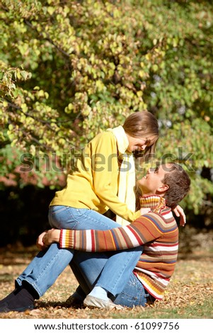Photo of happy couple relaxing in autumnal park - stock photo