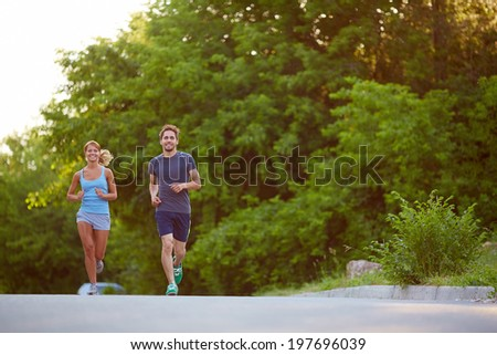 Photo of happy couple running outdoors - stock photo