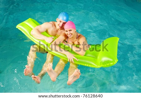Photo of happy couple with mattress in swimming pool - stock photo