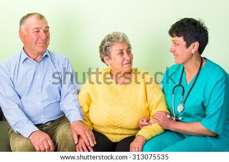 Photo of happy elderly couple with the doctor  - stock photo