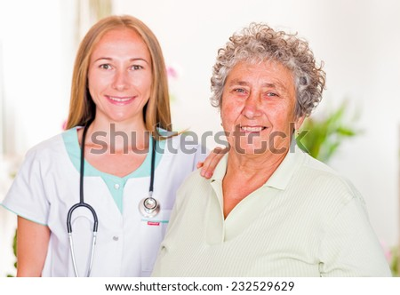 Photo of happy elderly woman with the young doctor - stock photo