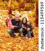 Photo of happy family in autumn park, parents with cheerful babies playing in fall forest, mother and father with daughter and son sitting in autumnal woods, happiness concept, pleasure time - stock photo