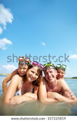 Photo of happy family looking at camera on resort - stock photo