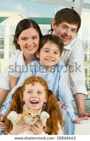 Photo of happy family members and their cute cat having fun - stock photo