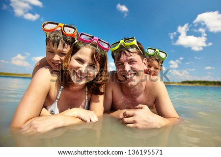 Photo of happy family of divers in water looking at camera - stock photo