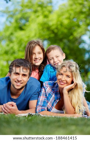 Photo of happy family of four relaxing on grass during summer rest - stock photo