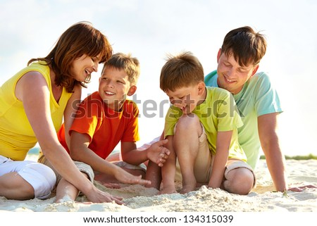 Photo of happy family playing with sand during summer rest - stock photo