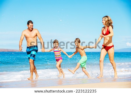 Photo of Happy Family Running Down the Beach - stock photo