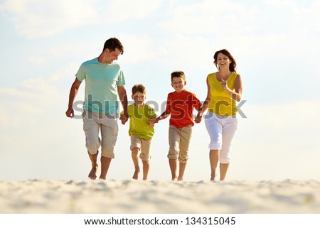 Photo of happy family running down the beach on summer - stock photo