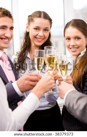 Photo of happy friends holding glasses full of champagne and smiling during party