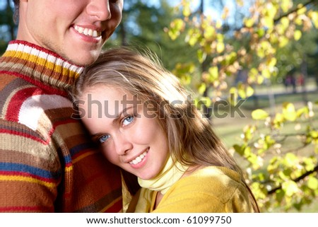 Photo of happy girl close to handsome male in autumnal park - stock photo