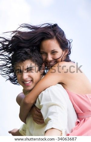 Photo of happy girl embracing handsome guy against blue sky at summer