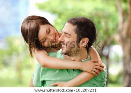 Photo of happy girl embracing handsome male outside - stock photo
